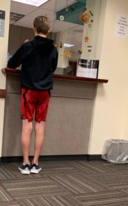 Teen standing at the doctors office check in desk.